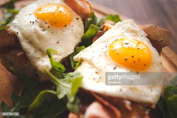 Fried eggs sunny side up on baguette, ham and arugula