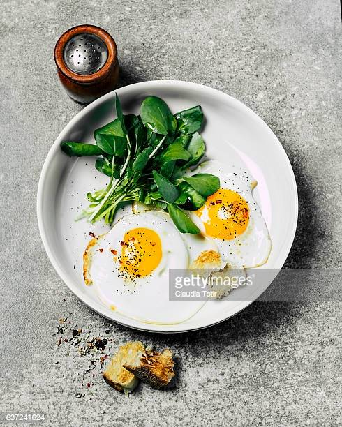 fried eggs with salad - fried eggs stock pictures, royalty-free photos & images