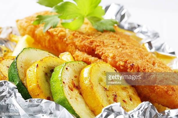 fried fish with zucchini and french fries - breaded stock photos and pictures