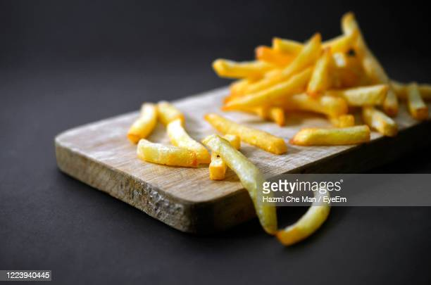 fried frech fries potato on wooden plate on black background - french fries stock pictures, royalty-free photos & images