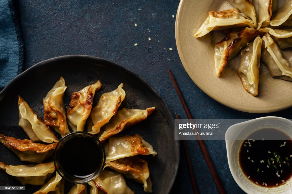 Fried gyoza dumplings with duck served with soy sauce ans sesame seeds. Dark blue concrete background : Stock Photo