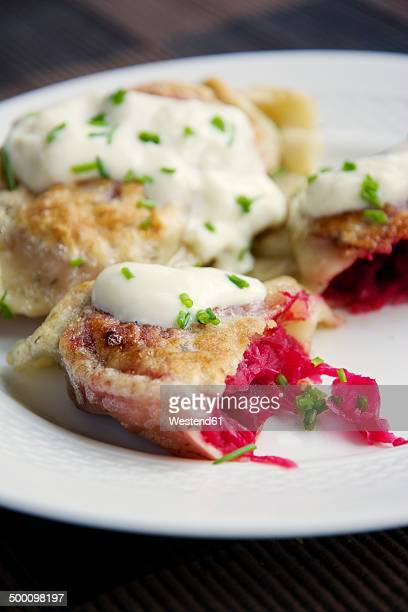 Fried herbed pierogi with a beet, sauerkraut and potato filling, served with soy yogurt and chives