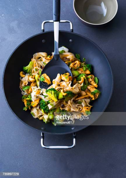 Fried noodles with chicken, broccoli and cashew nuts in a wok