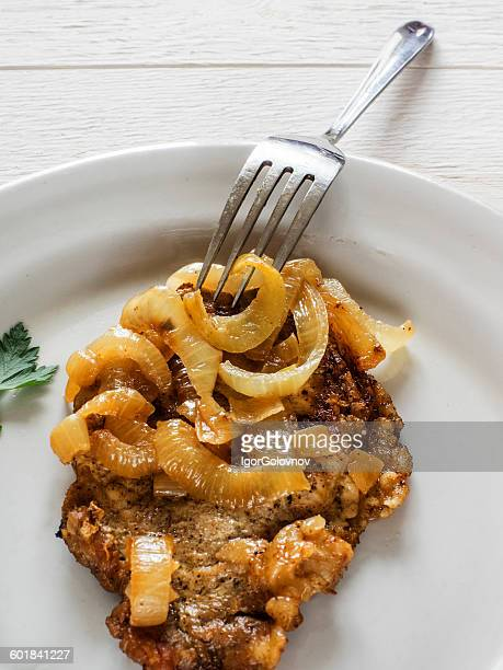 Fried pork chop on the bone with onions and a fork on plate