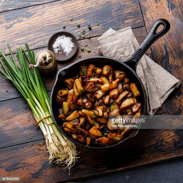 Fried potatoes roasted with porcini mushrooms in cooking pan on wooden background
