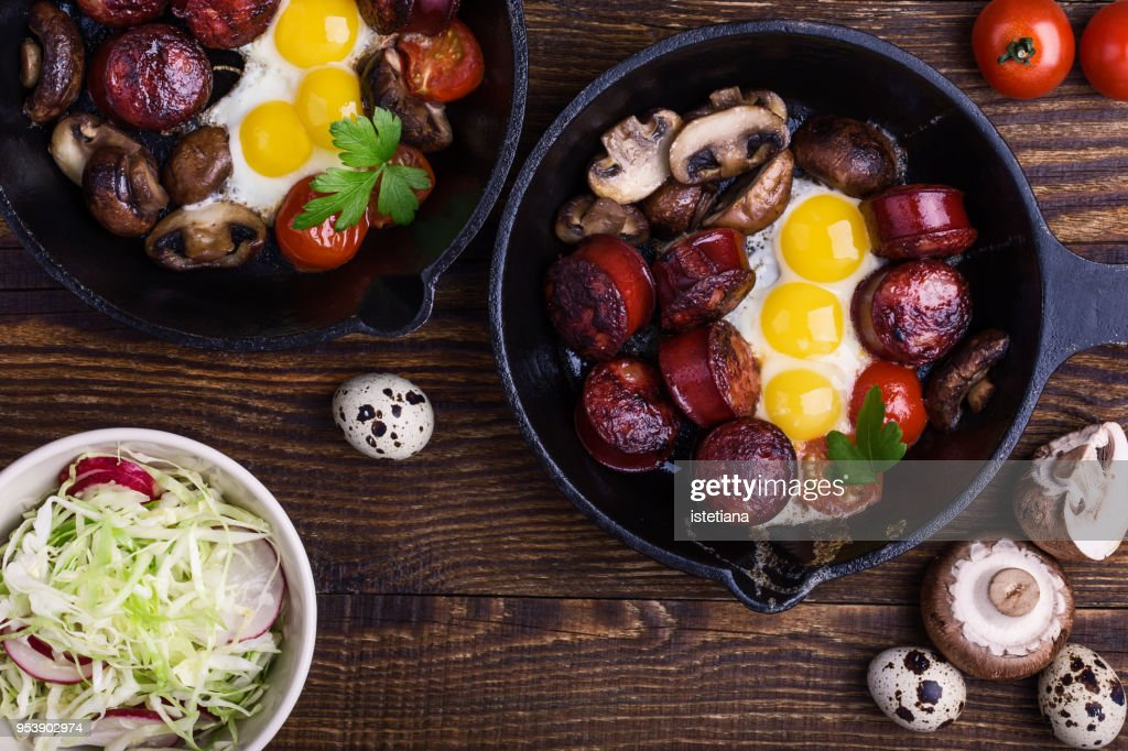 Fried quail eggs with sausages and mushrooms : Stock Photo