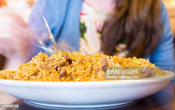 Fried rice on large white plate reflecting on dark brown wood table in front of woman holding a fork wearing a blue shirt with hair draped over her...