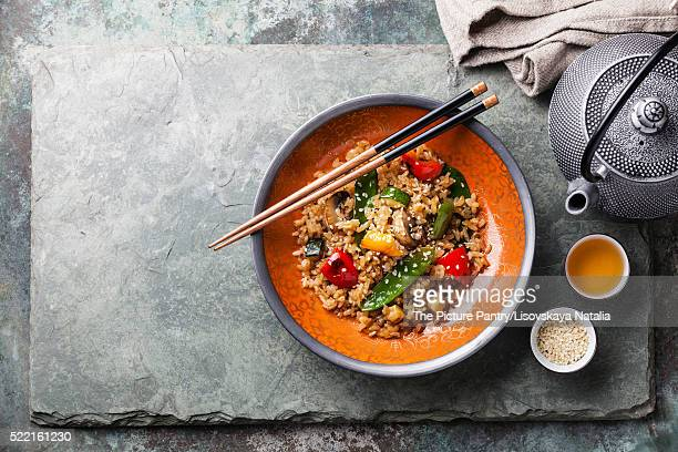 Fried Rice with vegetables in red bowl and green tea on stone sl
