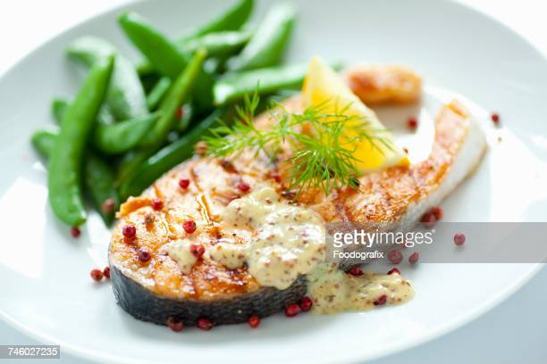 Fried salmon steak with sugar snap peas, honey and mustard sauce and red peppercorns