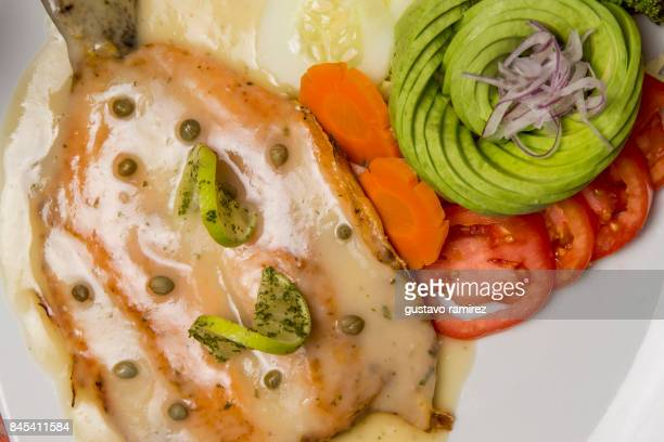 fried salmon with cream and avocado salad and pepper