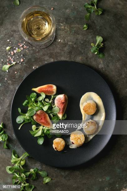 Fried scallops with lemon figs sauce and green salad served on black plate with glass of white wine over old dark metal background Top view space...
