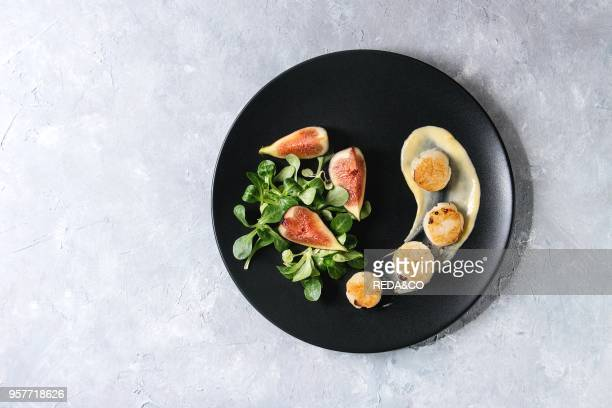 Fried scallops with lemon, figs, sauce and green salad served on black plate over gray texture background. Top view, copy space. Plating, fine dining.