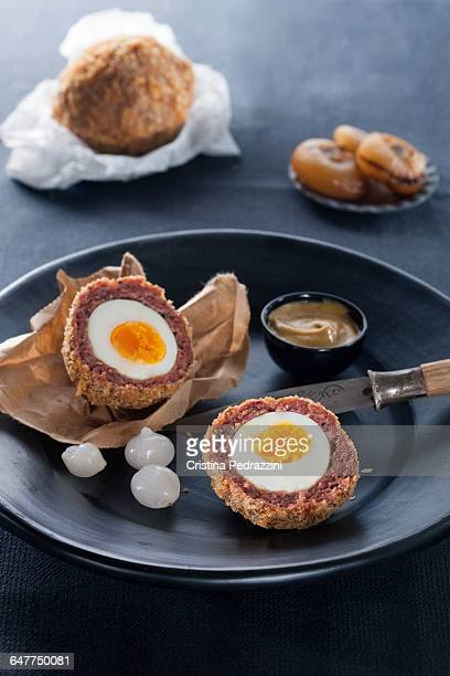 Fried Scotch eggs with pickled onions on a plate