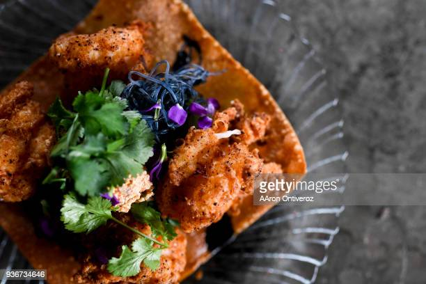 Fried shrimp prepared with bok choy squid ink rice noodles and pureed tofu at Rebel Restaurant on Wednesday March 21 2018