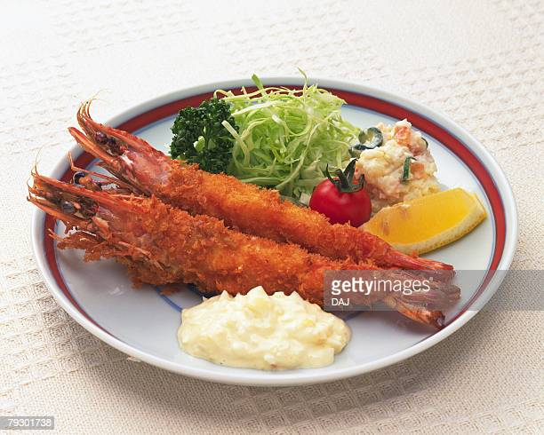 Fried shrimps on plate, high angle view, white background