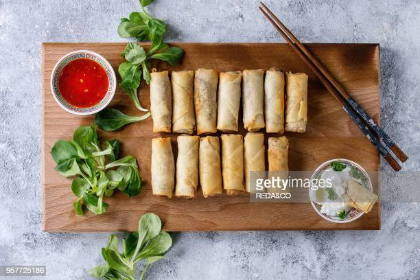 Fried spring rolls with red and white sauces served on wood serving board with fresh green salad and wooden chopsticks over gray blue texture...