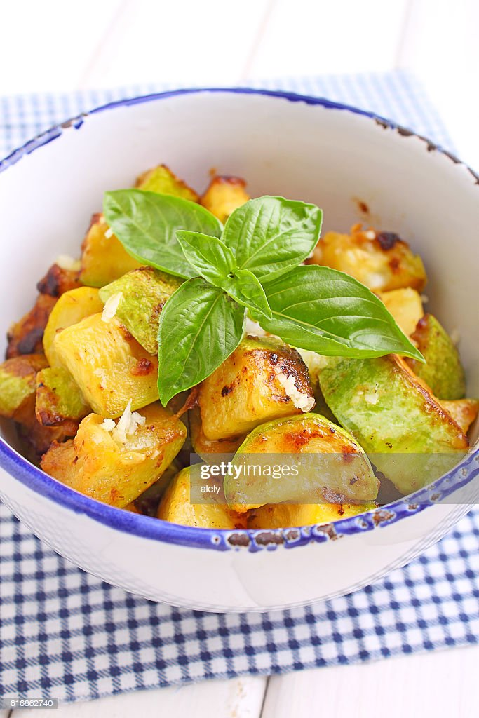fried zucchini with garlic and basil in white plate : Stock Photo
