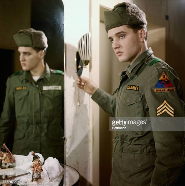 Friedberg, Germany: Wearing a serious expression, singer Elvis Presley points to his three stripes after he was promoted to acting Sergeant here...