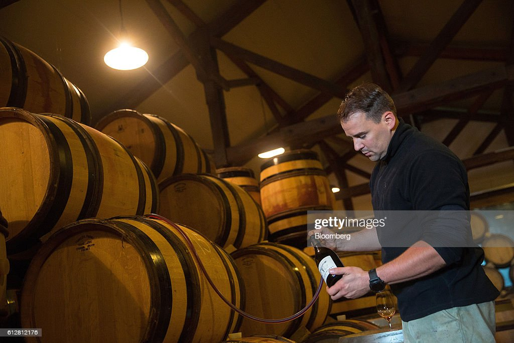 Friedrich Wilhelm Becker, co-owner of the Weingut Friedrich Becker Estate, syphons pinot noir wine from a barrel, also known as spaetburgunder, during tasting at the vintner's estate in Schweigen, Germany, on Tuesday, Oct. 4, 2016. Global warming has been good to German viticulture, with average temperatures up 1.4 degrees centigrade over the past 40 years, creating the perfect climate for notoriously finicky pinot noir vines. Photographer: Krisztian Bocsi/Bloomberg via Getty Images