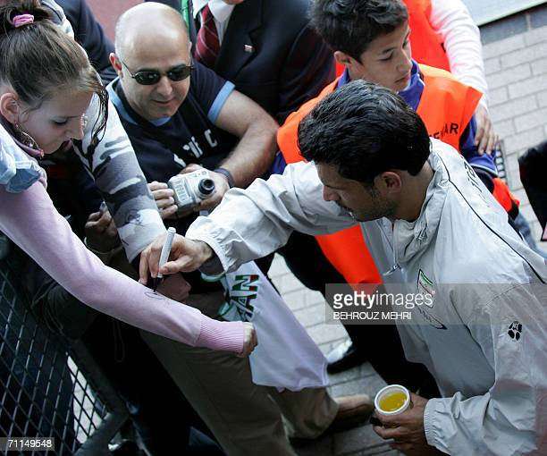 Iranian forward Ali Daei gives his autograph to a supporter after a team training session in Friedrichshafen Stadium 07 June 2006 Iran have their...