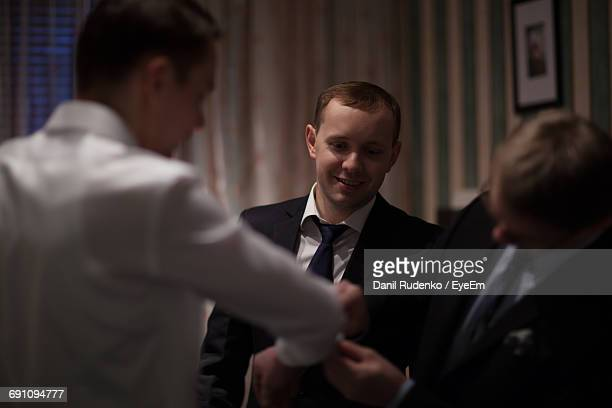 Friend Adjusting Cuff Link Of Bridegroom