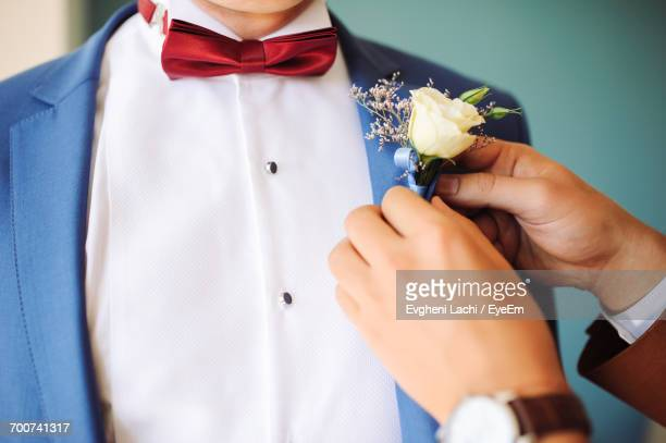 Friend Assisting Bridegroom While Wearing Boutonniere During Wedding