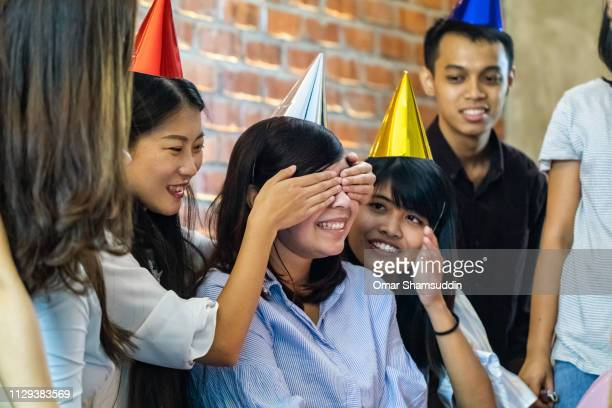 Friend covering eyes for birthday surprise