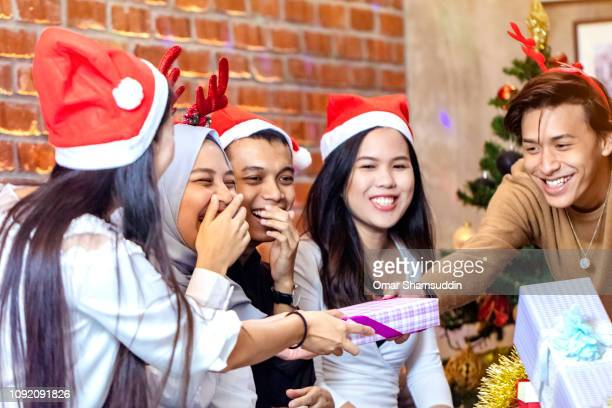 A friend handing over present during Christmas gathering with friends