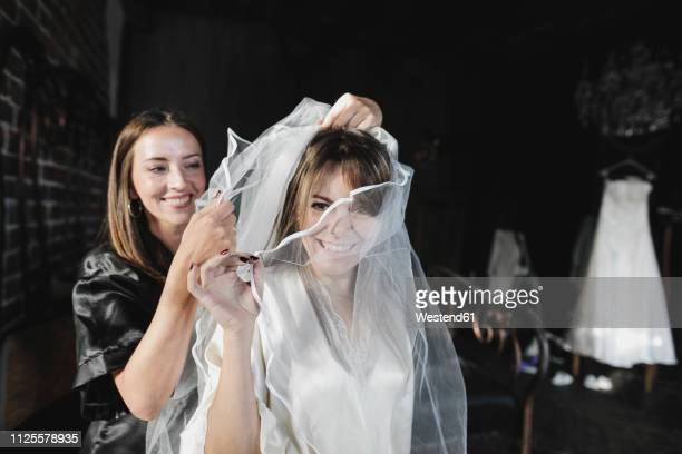friend helping women getting dressed for her wedding celebration - veil stock pictures, royalty-free photos & images