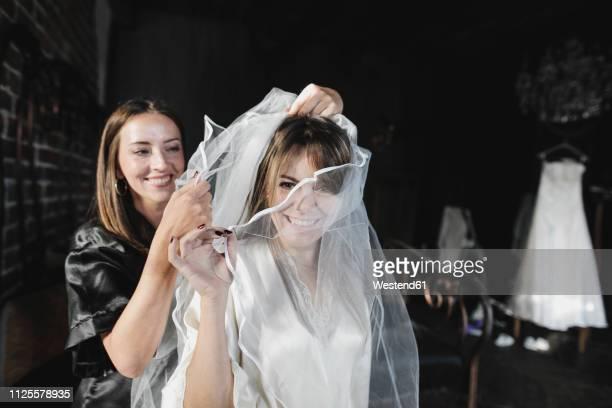 friend helping women getting dressed for her wedding celebration - wedding veil - fotografias e filmes do acervo