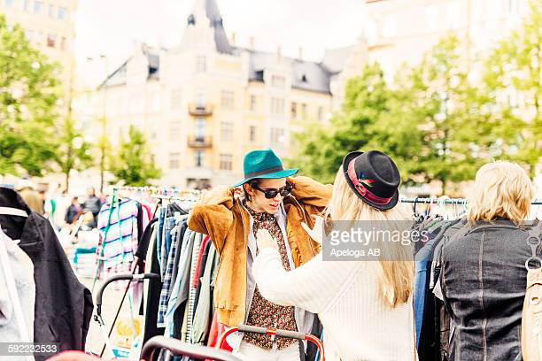 Friend helping young man in wearing jacket at flea market