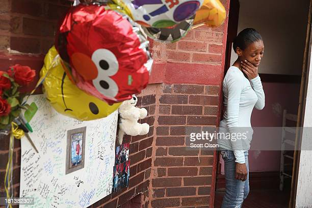 A friend of 25yearold Rubin Austin stands outside her home next to memorial placed on the spot where she found Austin dying from a gunshot wound...
