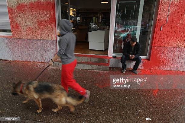 A friend of a coowner talks on a mobile phone while sitting outside the vandalized Schiller Backstube bakery as a woman with a dog walks by in...