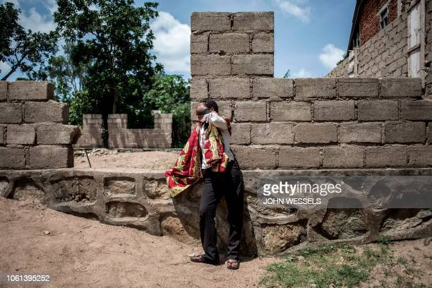 Friend of a victim reacts in mourning after the burned corpse of a friend was found underneath a house on November 14, 2018 in Beni. - The house was...