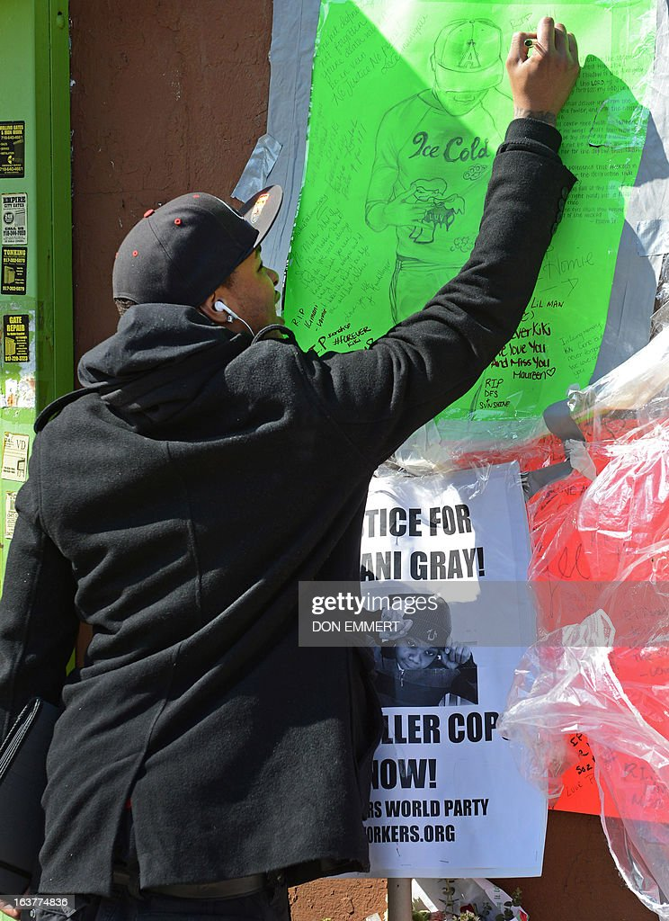 A friend of Kimani Gray signs a poster at a memorial for the 16-year-old boy March 15, 2013 in New York. Kimani Gray was shot by two police officers late on Saturday in Brooklyn's East Flatbush neighborhood after police said he pointed a handgun at them. Gray's family has denied the teen was armed. An autopsy revealed that Gray had been shot seven times, including three times in the back. Although the report did not detail the order in which the bullets struck Gray, the revelations increased tensions among the already furious community.