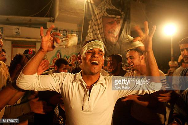 A friend of Palestinian refugee brothers Mahmoud Mansor and Mohammad Mansor sticks money on his head and holds more before he gives it for the grooms...