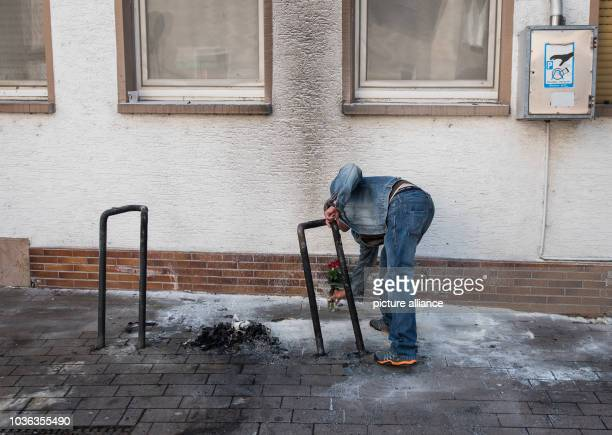 A friend of the homeless man that burned during the previous night in GrossGerau Germany lays flowers at the site of the incident 14 April 2017 The...