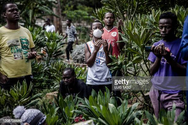 A friend of Yassin Hussein Moyo prays with a face mask on during Yassins burial at Kariokor Muslim Cemetery in Nairobi Kenya on March 31 2020...