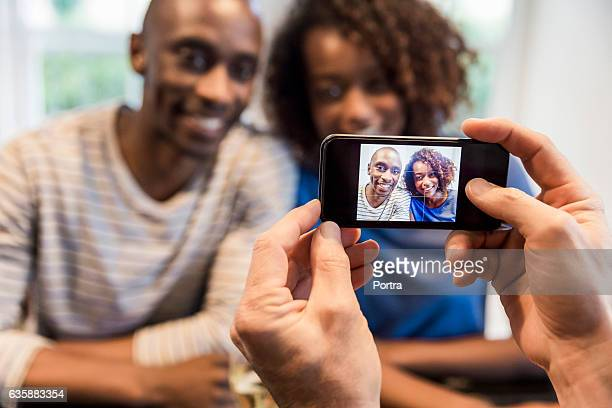 Friend photographing couple through smart phone