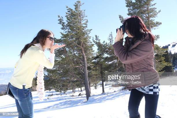 Friend Photographing Woman While Standing On Snow Field During Winter