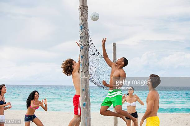 friend playing volleyball on the beach - beachvolleybal stockfoto's en -beelden