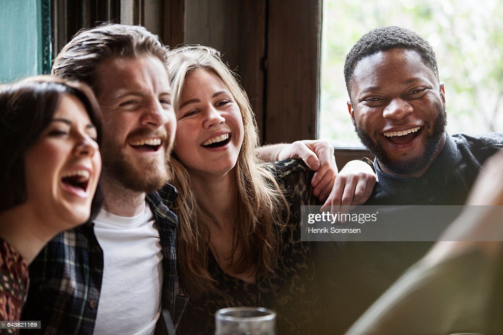 A group of friends in a pub posing for a picture having a good time