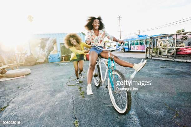 friend pushing carefree woman on bicycle - empurrar atividade física imagens e fotografias de stock