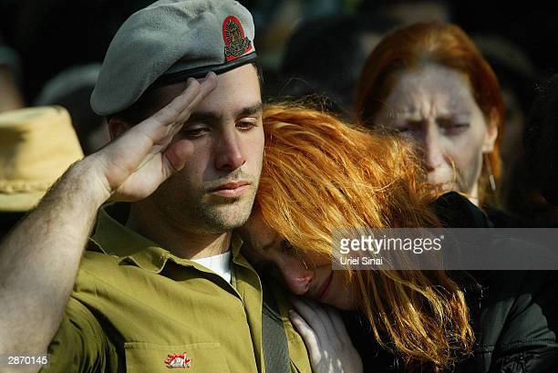 A friend salutes as the sister of killed Israeli soldier Zur Or rests her head on his shoulder as they mourn during his funeral at a cemetery January...
