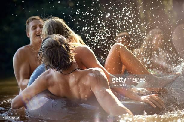 Friend splashing in water on rubber tube