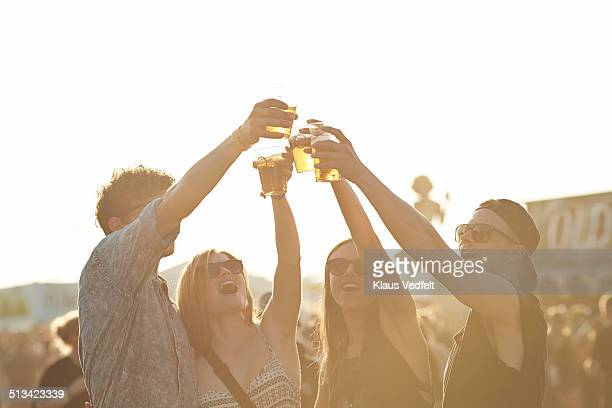 friend toasting in beer at outside festival - men friends beer outside stock pictures, royalty-free photos & images