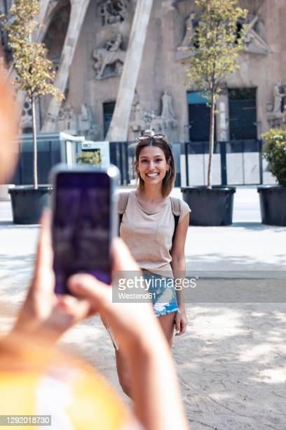 friend using mobile phone while taking photo of woman standing against sagrada familia at barcelona, catalonia, spain - familia stock-fotos und bilder