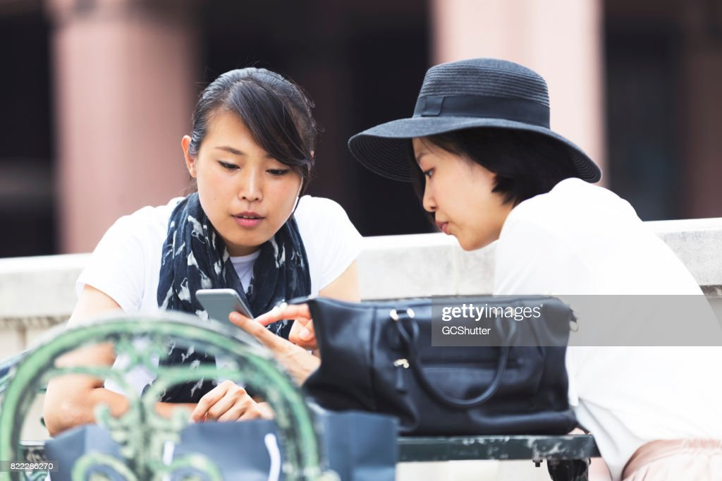 Friend using social media on a smart phone to pass the time at a cafe. : Stock Photo