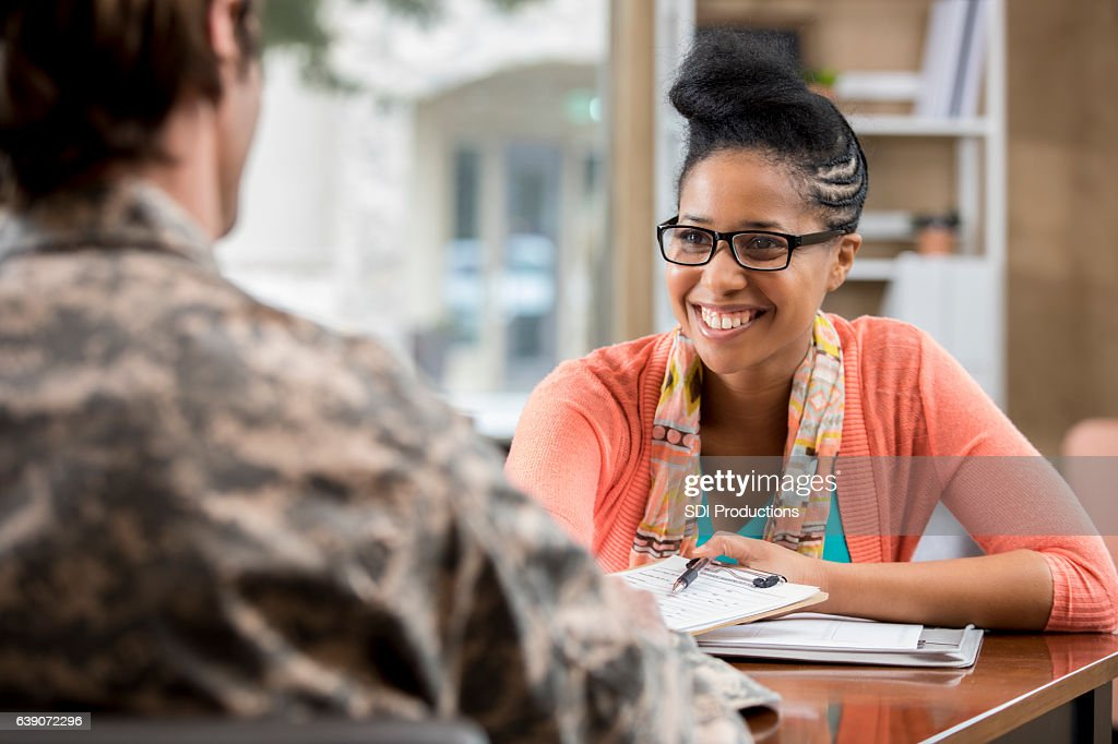 Friendly African American female military counselor talks with veteran : Foto de stock