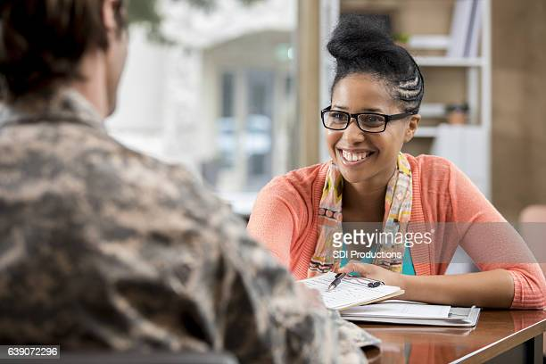 friendly african american female military counselor talks with veteran - military doctor stock photos and pictures
